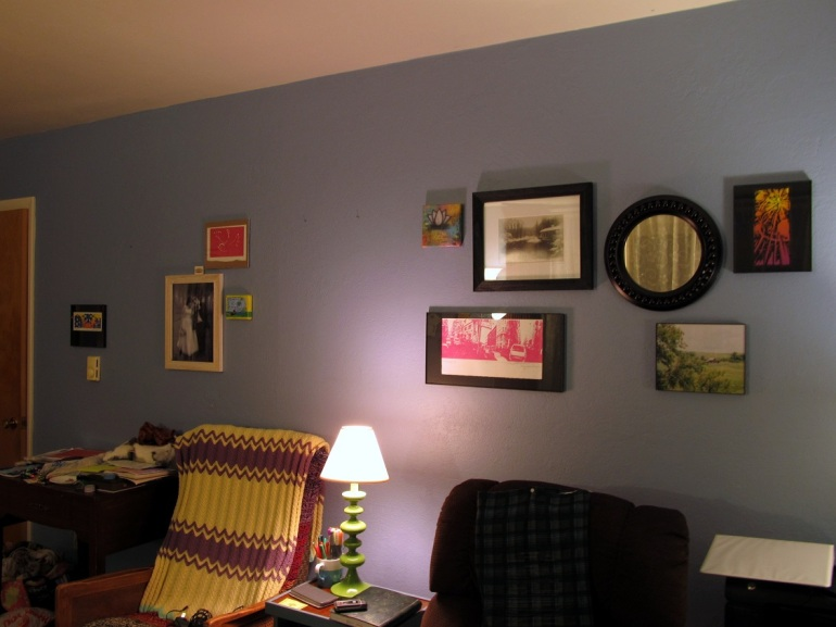 Our living room wall. Notice anything off? i mean besides the piles on my sewing machine.