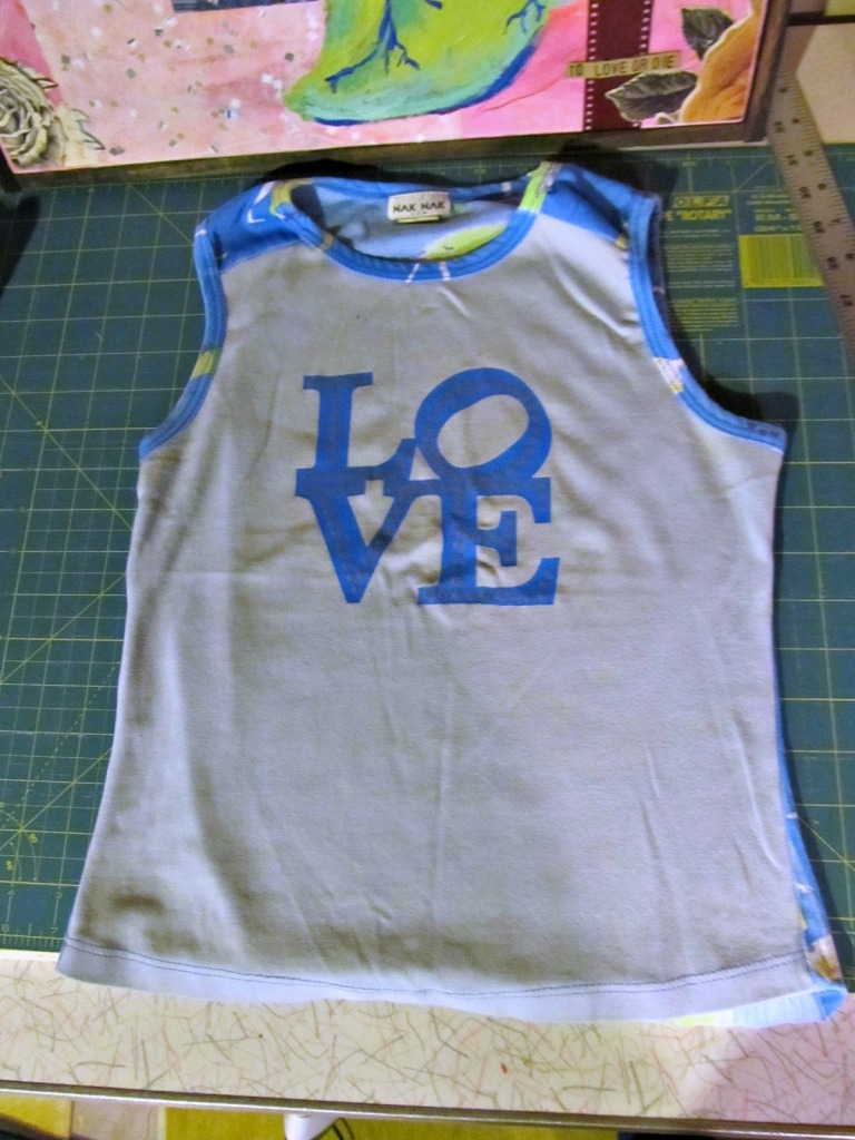 "This shirt was the starting point for all pages. After digging through my stash, I knew I wanted each page to have three different fabrics. I also wanted this whole ""love"" block to be visible. So I cut it out, added the other blues and based all pages sizes off that."