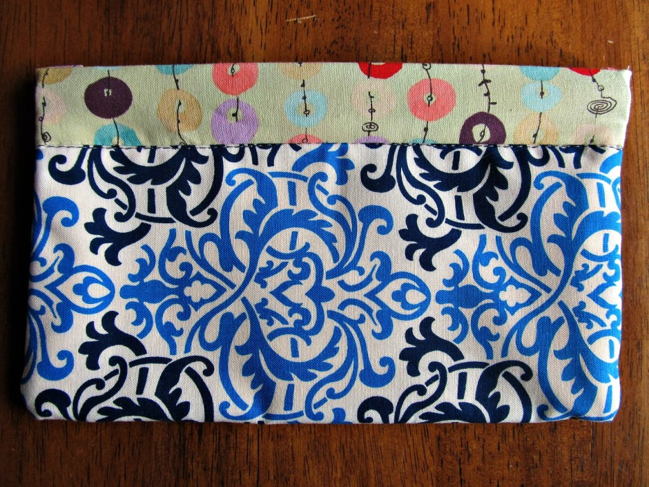 A simple sewn pouch for toting little goodies around in. It measures about 4.5 by 8 inches.